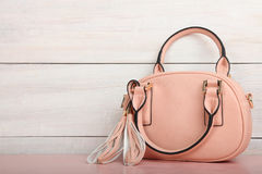 Female pink bag. On a desk on a wooden background Royalty Free Stock Photography