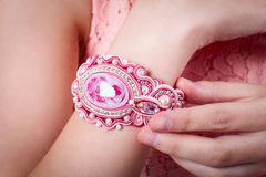 Female pink bracelet technique soutache on hand. Pink bracelet technique soutache on hand of girl in a pink dress, earrings and necklaces Royalty Free Stock Photo