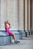 Female with pink dress  against a column Royalty Free Stock Image