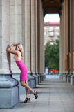 Female with pink dress stands against a column Royalty Free Stock Photos