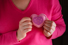 Female in pink give soft heart. Romantic concept. Female in pink holding soft heart symbol stock photo