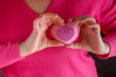 Female in pink give soft heart. Romantic concept. Female in pink holding soft heart symbol stock images