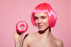 Female with pink hair holding doughnut Royalty Free Stock Photos