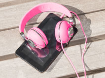 Female pink headphones and tablet pc Royalty Free Stock Photo