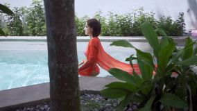 Female in a pink long dress swims in a blue pool under water. Pink fabric develops in water. Female in a pink long dress swims in a blue pool under water. Pink stock video footage