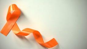 Female placing orange ribbon on table, leukemia awareness campaign, precaution. Stock photo royalty free stock photo