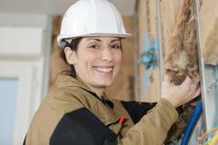 Female plasterer removing material. Female plasterer removing the material Royalty Free Stock Image