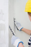Female plasterer repairs wall Royalty Free Stock Photos