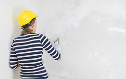 Female plasterer repairs wall Royalty Free Stock Images