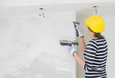Female plasterer repairs wall Stock Images
