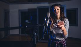 Female playback singer with mobile phone Royalty Free Stock Photos