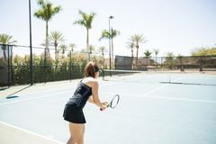 Female player serving the ball. Young woman playing tennis, serving the ball on court Royalty Free Stock Images