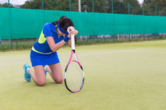 Female player is upset and  fell on her knees because of the los. Female player wearing a sportswear is upset and  fell on her knees because of the loss in Stock Image
