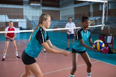 Female players playing volleyball in the court Stock Photography