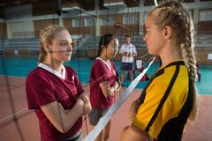 Female players standing with arms crossed and staring each other Royalty Free Stock Images