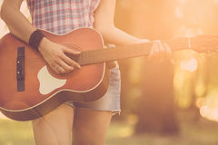 Female playing acoustic guitar outdoors. Close up of female hands playing acoustic guitar in nature. Retro, music, lifestyle concepts Royalty Free Stock Photography