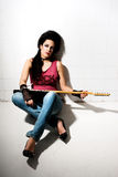 Female playing electric guitar. Punk female playing electric guitar on underground background Royalty Free Stock Photo