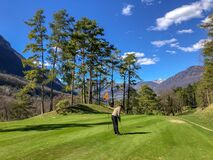 Female playing golf on a beautiful grass-covered course under the blue sky