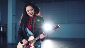 Female playing the guitar in hangar stock footage