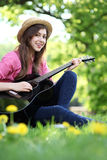 Female playing guitar in park Royalty Free Stock Photography