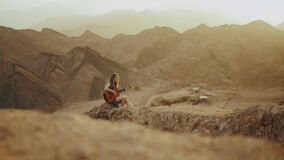 Female playing guitar and singing in desert landscapes, desert mountains background, slow motion, 4k