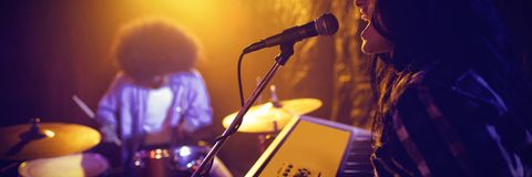 Female playing piano by drummer in nightclub. E view of female playing piano while performing with drummer in nightclub Stock Photos