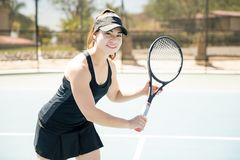 Female playing tennis on court. Portrait of beautiful professional tennis player playing a match on outdoor court Stock Images