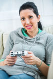 Female playing video-games concentrating on sofa Royalty Free Stock Images