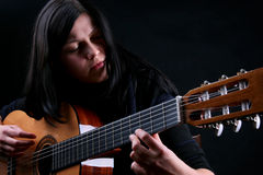 The female plays on the guitar Stock Photography