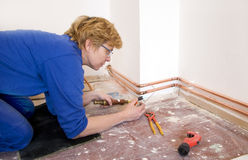 Female plumber. Femal plumber soldering copper pipes on a construction site Stock Photography