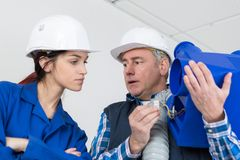 Female plumber with apprentice. Female royalty free stock photos