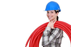 Female plumber carrying hose Royalty Free Stock Image