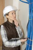 Female plumber checking canalisation pipes construction site. Female plumber checking canalisation pipes of a construction site royalty free stock photos