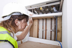 Female plumber examining pipes of central heating boiler Royalty Free Stock Images