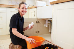 Female plumber holding a u-bend pipe for a kitchen sink Royalty Free Stock Photos