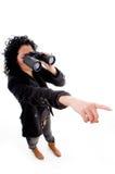 Female pointing while looking through binocular Royalty Free Stock Image