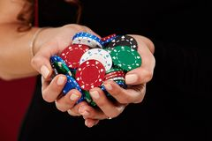 Female Poker player with paint white nails hold her poker chips to make a bet. Gambling and casino business concept Royalty Free Stock Photo