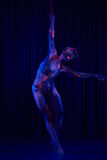 Female pole dancer in bright neon colours under ultraviolet Royalty Free Stock Images