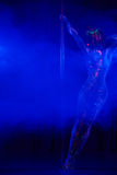 Female pole dancer in bright neon colours under ultraviolet Stock Images