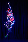 Female pole dancer in bright neon colours under ultraviolet Royalty Free Stock Photography