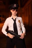 Female police officer. With gun at night Stock Photo