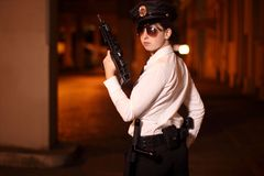 Female police officer. With gun at night Stock Photos