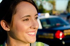 Female police officer. A close up of a smiling female police officer with her patrol car in the background Stock Photos