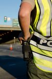 Female police officer. A female police officer with her hand on her radio while wearing a reflective vest doing traffic control Royalty Free Stock Photos