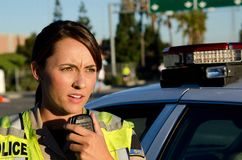 Female police officer. A female police officer talks on the radio while standing next to her patrol car Stock Photo