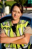 Female police officer. A female police officer with a frown on her face as she crosses her arms in front of her partrol car Stock Photos