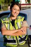 Female police officer. A female police officer smiling as she crosses her arms in front of her partrol car Stock Photography