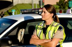 Female police officer. A female police officer crosses her arms as she stands next to her patrol car Stock Images