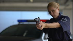 Female police officer aiming gun into criminal, dangerous work, crime prevention. Stock footage stock footage