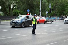 Female police officer controls car traffic. Warfsaw, Poland. June 10, 2017.  Female police officer controls car traffic before the match Poland-Romania Royalty Free Stock Image